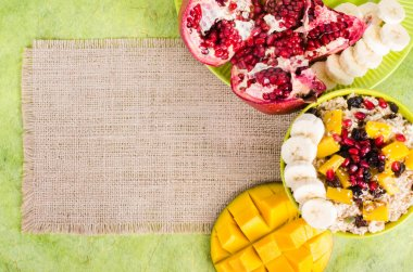 Oatmeal with mango, banana, seeds of pomegranate, raisins, dried fruits and sesame on canvas and green background. Healthy vegetarian breakfast. Free space for your text.