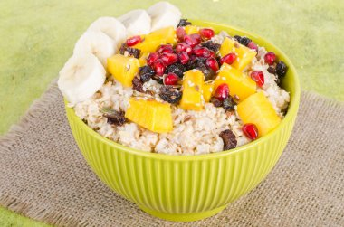 Oatmeal with mango, banana, seeds of pomegranate, raisins, dried fruits and sesame on canvas and green background. Healthy vegetarian breakfast.