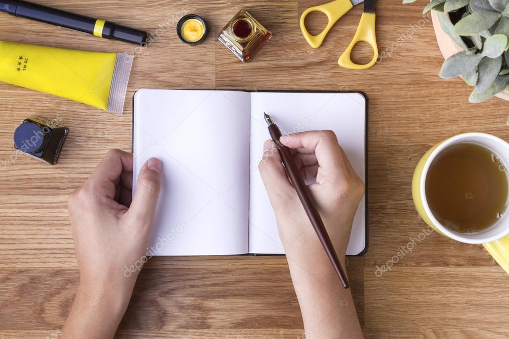 Hand with pen writing on blank notepad and yellow objects
