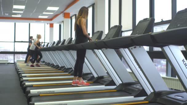 Mädchen trainiert im Fitnessstudio auf einem Laufband