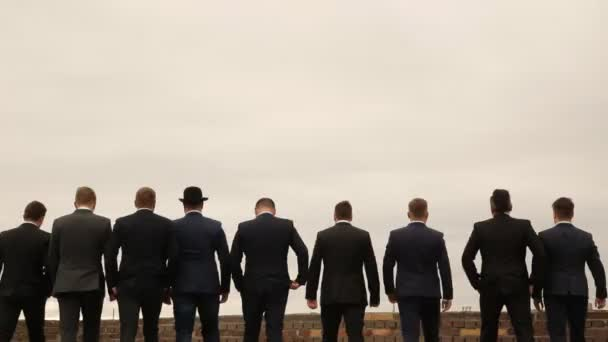 nine men in suits having fun