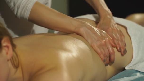 mladá žena dostává masáž zad