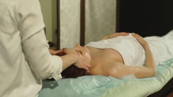 hübsche junge schwangere Frau tun, Gesichtsmassage