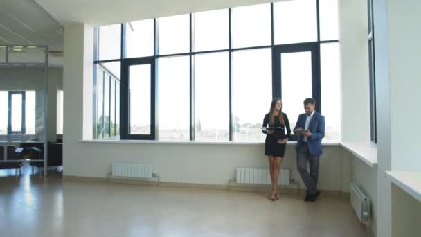 podnikatelka a podnikatel stojící v kanceláři a diskutovat podnikatelský plán
