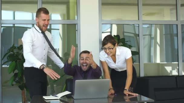 Business-Team diverse multiethnischen junger Menschen sitzen an einem Tisch im Büro als th ausgelassen jubeln begeistert
