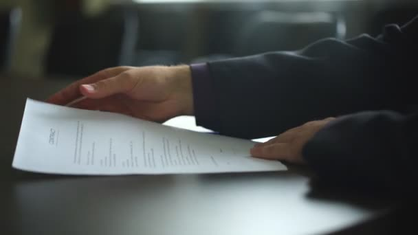 Low angle view of male hand signing contract or subscription form with a pen on a rustic wooden desk