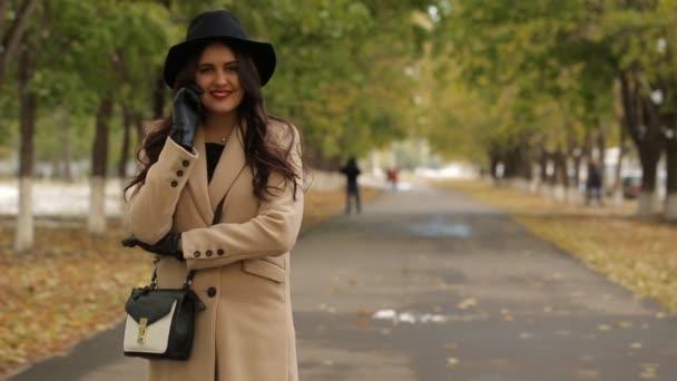 Šťastná dívka chodí v podzimní alej a mluví po telefonu