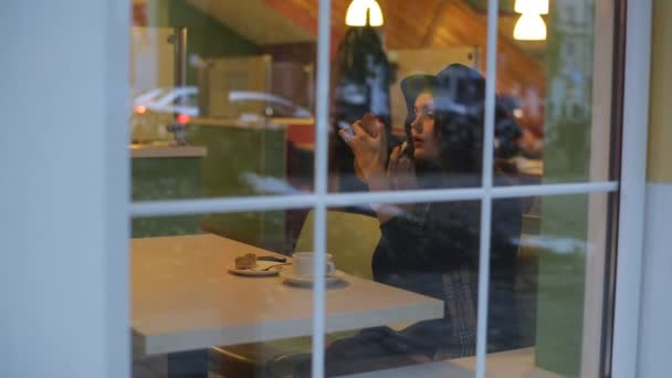 Mladá krásná žena sedí v kavárně a rtěnka