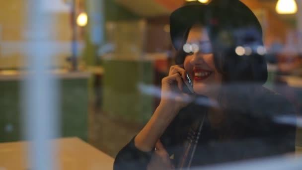 Mladá krásná žena sedí v kavárně a mluví po telefonu