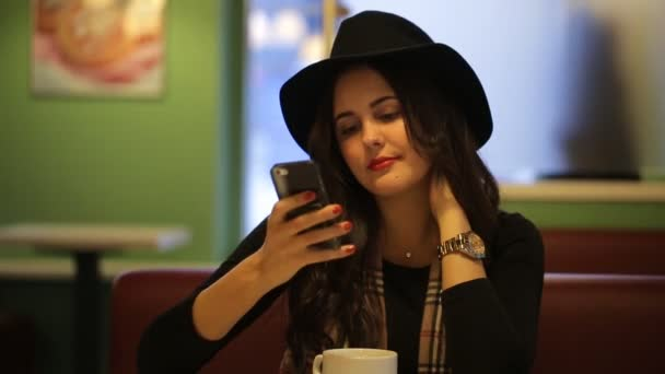 Girl sitting in cafe and ase your phone