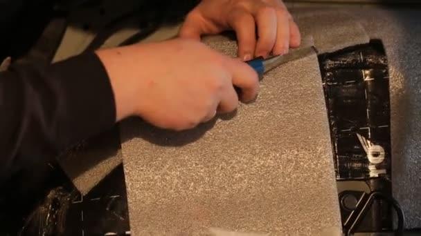 člověk připravuje materiál pro zvukové izolace