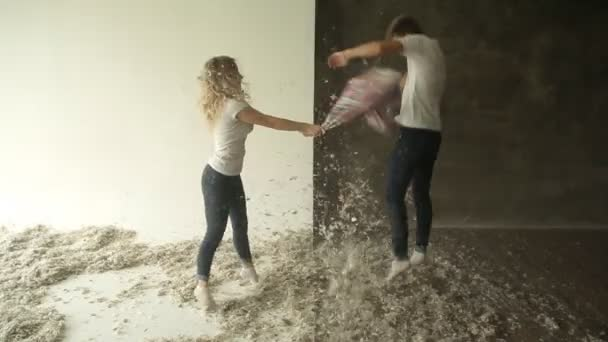 Young couple fighting pillows in the studio