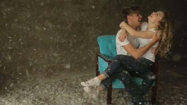 schönes Paar sitzt auf einem Stuhl im Studio küssen