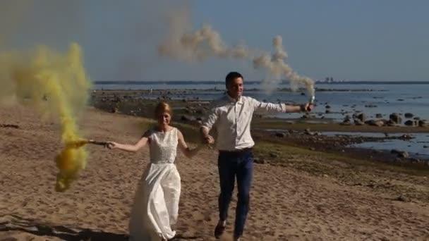 Coppie di nozze viene eseguito fumo di colore sulla spiaggia