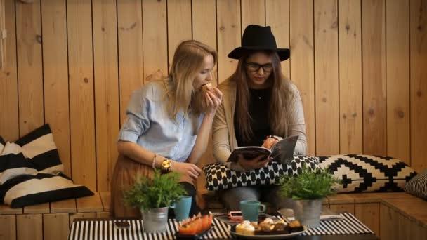 zwei junge schöne Mädchen trinken Tee und lesen Zeitschrift