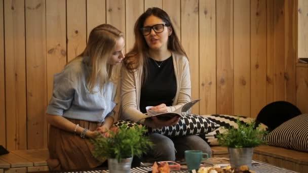 Due ragazze che leggono la rivista e smilling in caffè