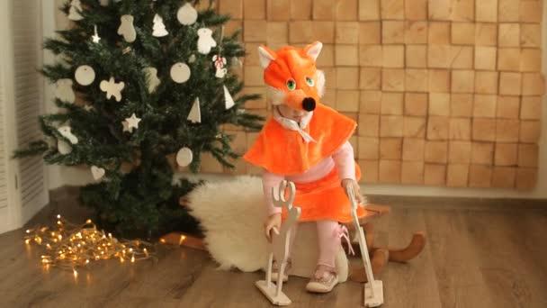 Bambino bambina vestita in tuta di volpe vicino allalbero di Natale