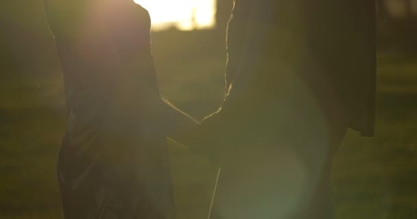 Holding hands portrait young couple in love park sunset slow motion lifestyle