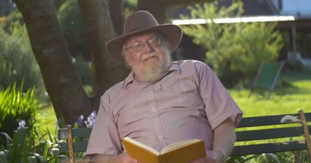 Retired elderly man relaxing outdoors reading a book enjoying retirement