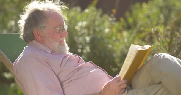 Retired elderly man relaxing outdoors reading a book enjoying retirement