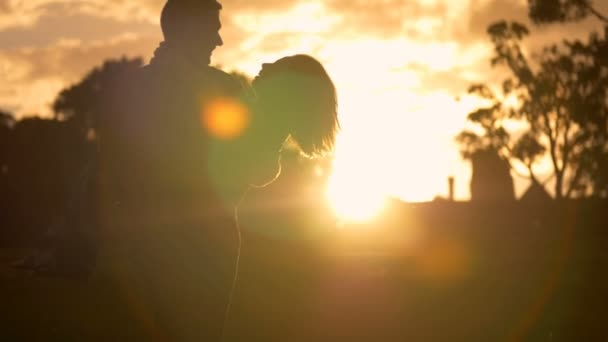 Dreamy romantic heterosexual couple in love hug in the glow of a sunset