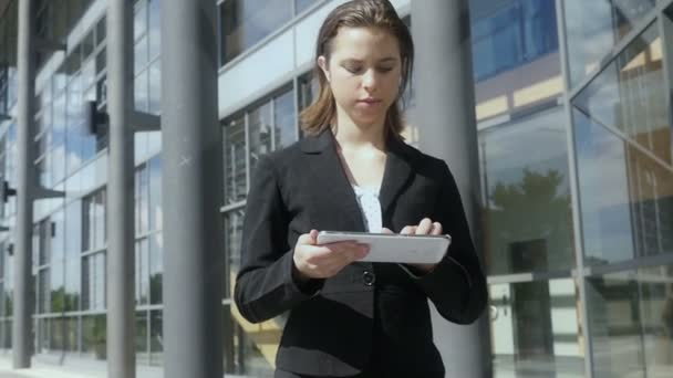 Business woman walking while using tablet