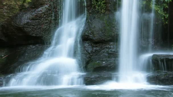 Waterfall over rocks with green moss in rainforest