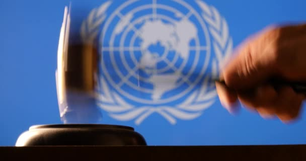 Judge calling order with hammer gavel in United Nations court flag background