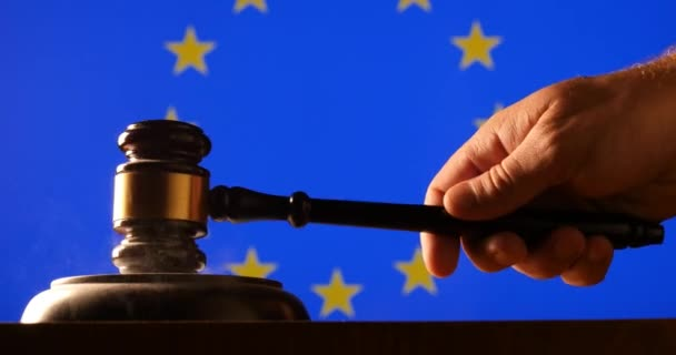 Judge calling order with hammer and gavel in EU court with flag background