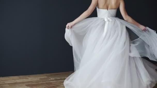 Beautiful young bride in white wedding dress spinning. Beautiful girl smiling