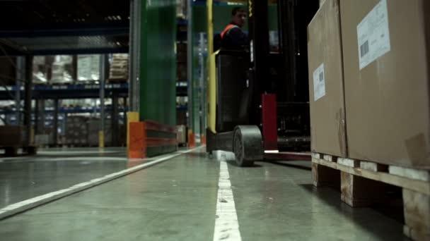 Muž na vozík přepravující náklad z jednoho skladu do jiného