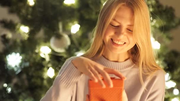 Krásy dívka otevírá vánoční krabičky a hledí do kamery