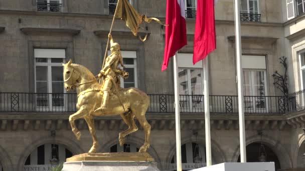 Paris, Frankreich - ca. Mai 2016: Gedenken mit Fahnen in der Nähe von vergoldeter Bronze Reiterstandbild Darstellung Saint Jeanne d Arc (Johanna von Orléans). Place des Pyramides, Paris, Frankreich, ultra-HD-4k, Real-time