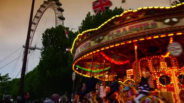 LONDON: Amusement park carousel with beautifully painted wooden horses near London Eye in London, UK. London Eye is the tallest Ferris wheel in Europe at 135 meters. ultra hd 4k, real time