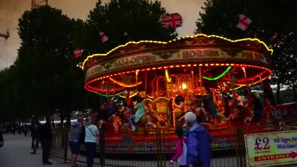 Londýn: karusel zábavní park s nádherně pomalovanými dřevěnými koňmi poblíž londýnského oka v Londýně. London Eye je nejvyšší Ferrisův volant v Evropě na 135 metrů. Ultra HD 4k, reálný čas