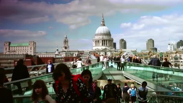 LONDON : People walking over Millennium bridge in London, UK  It's a  suspension bridge with a total length of 370 metres (1,214 ft) and a width  of 4 metres (13 ft) real time, ultrahd 4k,zooming