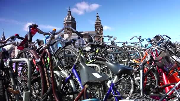 AMSTERDAM : Bicycles parked in row on Amsterdam that is one of the most eco-friendly cities in the world. Located in the Old Centre area, St Nicholas is the citys major Catholic Church.4k