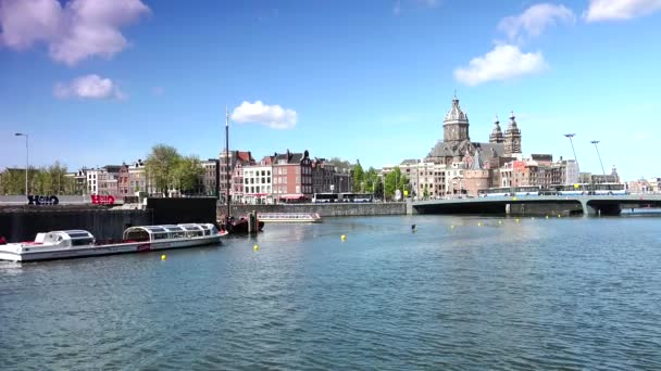 AMSTERDAM : St Nicholas, located in the Old Centre area, is the citys major Catholic Church. Rush hour with St. Nicolas Church in background.ULTRA HD 4K, REAL TIME