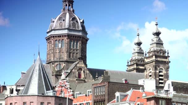 Amsterdam: St. Nicholas, ležící ve starém centru města, je hlavní katolickou církví. Hodina spěchá s kostelem svatého Nicolase v pozadí. Ultra HD 4k, reálný čas