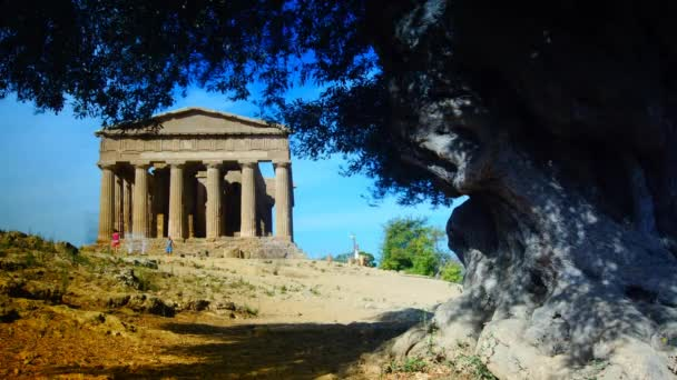 Agrigento,Sicily,Italy: tourists visiting Concordia temple with beautiful sky and statue of angel in front in the Valley of the Temples, Agrigento, Sicily island, Italy, time lapse,4k