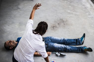 girl assisting an unconscious man with defibrillator and CPR