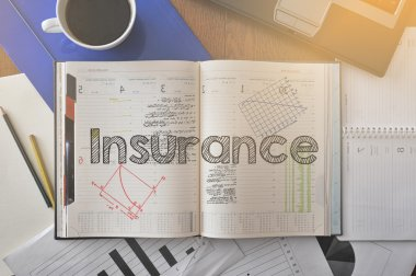 Notebook with text inside Insurance on table with coffee and some diagrams