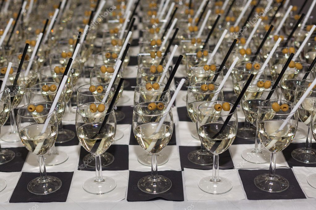 glasses with an aperitif and olives on black-white tablecloth