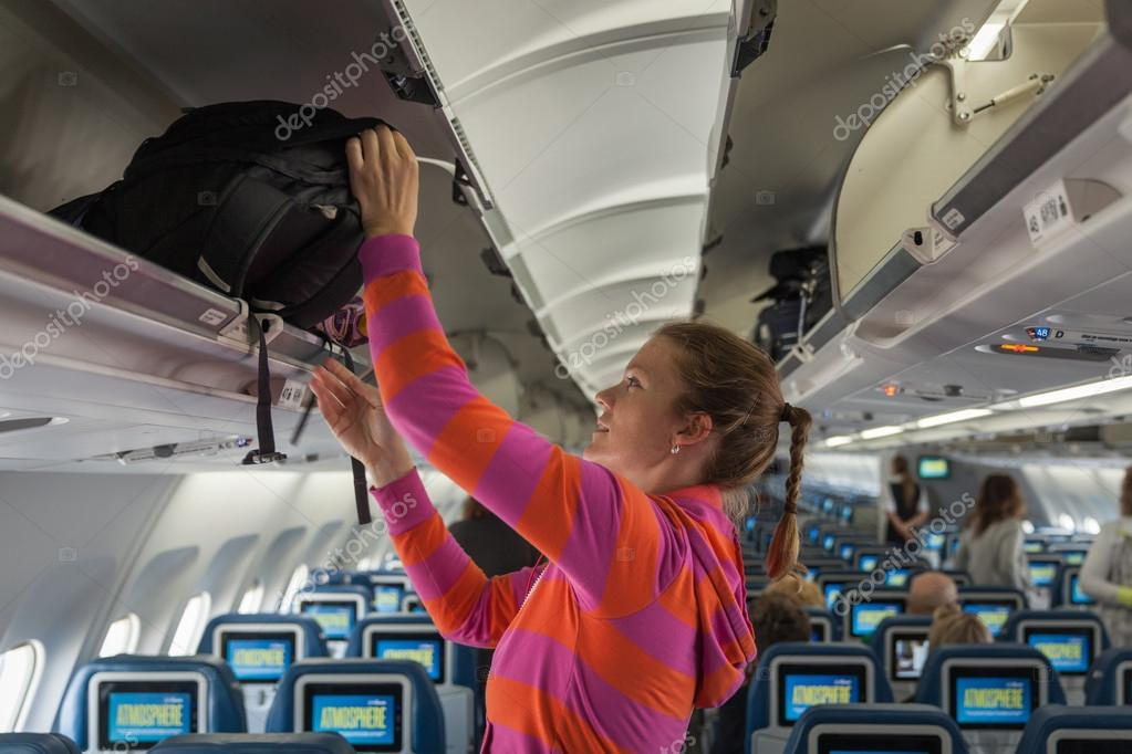 The young girl placed her hand luggage into the compartment on t