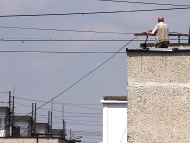 technicain stand on a roof to connect fiber-optic cables. Moscow.