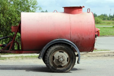 large red watering barrel for  streets hitched to the tractor in the Gatchina Leningrad region