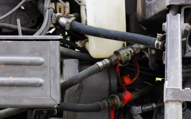 hoses, engine and spare parts inside the hood of the tractor