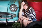 Fotografie Frau in einem Cap sitzt müde in der Garage in der Nähe von retro Auto mit Werkzeugen. Mädchen mit Zangen und ergriff den Kopf