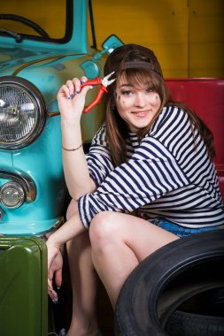 young attractive woman in a baseball cap sits in the garage near the retro car with tools. Girl holding pliers
