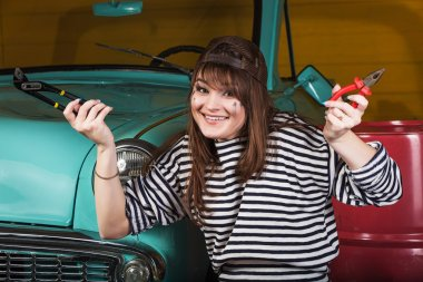 cheerful woman sits in the garage near the retro car with tools. Girl holding pliers and an adjustable wrench